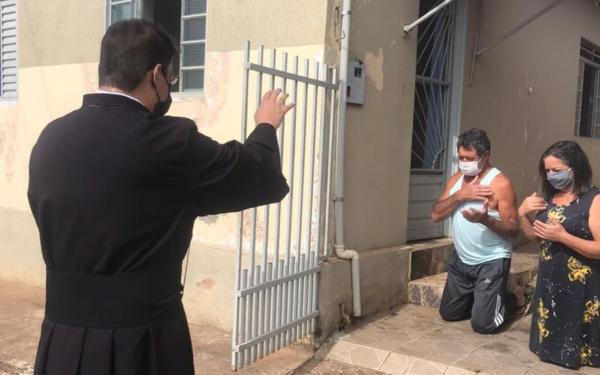 Padre caminha por ruas e abençoa moradores de casa em casa em MG